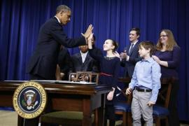 U.S. President Barack Obama (L) high fives children who wrote him letters about guns and gun control before sitting down to sign executive orders on a series of proposals to counter gun violence during an event at the White House in Washington